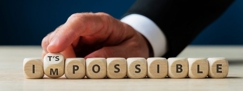Word impossible spelled on wooden cubes with male finger flipping letter M to make it a Its possible sign.